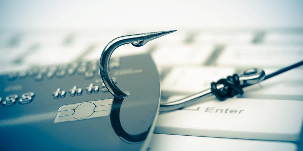 Hook in a credit card on a keyboard to represent a phishing scam.